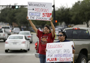 Photo - Yolanda Blue Horse, left, and Diana Parton, right, a member of the Caddo Nation, protest with others before an NFL football game between the Dallas Cowboys and Washington Redskins, Sunday, October 13, 2013, in Arlington, Texas. (AP Photo/LM Otero)
