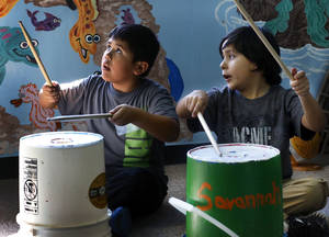 "Photo - CHILD / KIDS: Francisco Ruiz, left, and Joseph Mijares beat on empty buckets with drumsticks during a music session led by Armando Rivera.  Church volunteers work with children at this week's  fall break art and music camp at Hillcrest Fuente de Vita on Tuesday, Oct. 16, 2012.  The camp, called ""Where the Wild Things Are"" , is sponsored by St. Luke's United Methodist Church in Oklahoma City.     Photo by Jim Beckel, The Oklahoman"