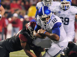 photo -   Kentucky quarterback Morgan Newton (12) is brought down by Arkansas linebacker Jarrett Lake, left, during the second quarter of an NCAA college football game in Fayetteville, Ark., Saturday, Oct. 13, 2012. (AP Photo/April L. Brown)