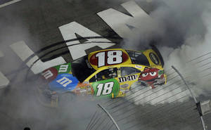 Photo - Sprint Cup Series driver Kyle Busch (18) celebrates after winning the NASCAR Sprint Cup Series auto race at Atlanta Motor Speedway in Hampton, Ga., Sunday, Sept. 1, 2013. (AP Photo/John Bazemore)