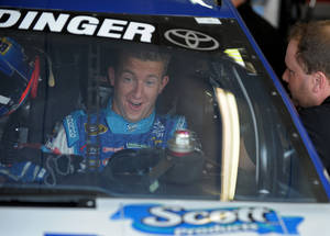 Photo - Driver AJ Allmendinger smiles as he straps into his car in the garage area before practice for Sunday's NASCAR Sprint Cup Series auto race at Atlanta Motor Speedway, Saturday, Aug. 31, 2013 in Hampton, Ga. (AP Photo/David Tulis)