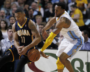 photo - Denver Nuggets guard Andre Iguodala, right, swats the ball out of the hands of Indiana Pacers guard Orlando Johnson as he drives to the net in the first quarter of an NBA basketball game in Denver on Monday, Jan. 28, 2013. (AP Photo/David Zalubowski)