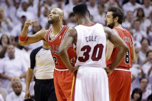 Photo - Chicago Bulls forward Taj Gibson, left, reacts after he was ejected during the second half of Game 2 of their NBA basketball playoff series in the Eastern Conference semifinals against the Miami Heat, Wednesday, May 8, 2013, in Miami. Chicago's Marco Belinelli and Miami's Norris Cole (30) stand by. The Heat won 115-78. (AP Photo/Lynne Sladky)