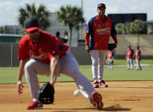 Photo - Former St. Louis Cardinals shortstop and Major League Baseball Hall of Famer Ozzie Smith, right, watches as Matt Carpenter works out at third base during spring training baseball practice Tuesday, Feb. 18, 2014, in Jupiter, Fla. (AP Photo/Jeff Roberson)