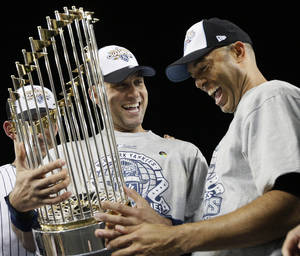 "Photo - FILE - In this Nov. 4, 2009, file photo, New York Yankees' Derek Jeter, left, and Mariano Rivera look at the championship trophy after winning the Major League Baseball World Series against the Philadelphia Phillies, in New York. Jeter says he will retire after this season ""with absolutely no regrets,"" ending one of the greatest careers in the history of baseball's most storied franchise.The 39-year-old New York captain posted a long letter on his Facebook page Wednesday, Feb. 12, 2014,  saying that 2014 will be his final year. (AP Photo/David J. Phillip, File)"