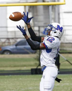 Photo - Millwood's Dametric Sanders catches a pass and runs for a touchdown during the 2010 Soul Bowl. Sanders has moved to the quarterback position. Photo By Paul Hellstern, The Oklahoman Archive