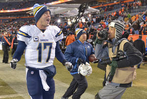 Photo - San Diego Chargers quarterback Philip Rivers (17) shouts to fans as he runs off the field after beating the Denver Broncos 27-20 in an NFL football game, Thursday, Dec. 12, 2013, in Denver. (AP Photo/Jack Dempsey)