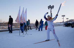 Photo - In this photo provided by Olympictorch2014.com torch bearer Luisa Noskova skis with an Olympic torch on the embankment of the Tura River during the Olympic torch relay in Tyumen, western Siberia, Russia, Wednesday, Dec. 11, 2013. The 65,000-kilometer (40,389 mile) Sochi torch relay, which started on Oct. 7, is the longest in Olympic history. The torch has traveled to the North Pole on a Russian nuclear-powered icebreaker and has even been flown into space. (AP Photo/Olympictorch2014.com)