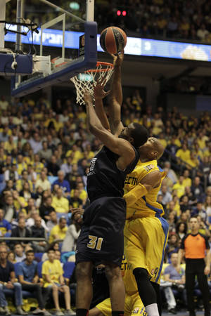 Photo - Emporio Armani Milan's Gani Lawal of USA, left, goes for the basket past Maccbi Tel Aviv's Alex Tyus during EuroLeague Basketball Group D playoffs game in Tel Aviv, Israel, Monday, April 21, 2014. (AP Photo/Ariel Schalit)