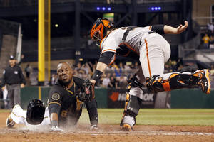 Photo - Pittsburgh Pirates' Starling Marte, left, scores ahead of the tag by San Francisco Giants catcher Buster Posey in the ninth inning of a baseball game in Pittsburgh, Tuesday, May 6, 2014. Marte was called out initially by home plate umpire Quinn Wolcott, but the call was overturned upon review. It was a walk-off triple, and an error, that allowed Marte to score. The Pirates won 2-1. (AP Photo/Gene J. Puskar)