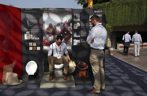 Photo - In this Friday, March 21, 2014 photo, an exhibitor from Loughborough University demonstrates the use of a toilet during Reinvent The Toilet Fair in New Delhi, India. Scientists who accepted the Bill & Melinda Gates Foundation's challenge to reinvent the toilet showcased their inventions in the Indian capital Saturday. The primary goal: to sanitize waste, use minimal water or electricity, and produce a usable product at low cost. India is by far the worst culprit, with more than 640 million people defecating in the open and producing a stunning 72,000 tons of human waste each day - the equivalent weight of almost 10 Eiffel Towers or 1,800 humpback whales. (AP Photo/Tsering Topgyal)