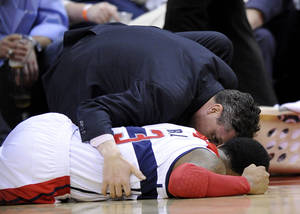 photo - Washington Wizards shooting guard Bradley Beal (3) lies on the court after being injured during the second half of an NBA basketball game against the Philadelphia 76ers, Sunday, March 3, 2013, in Washington. The Wizards won 90-87. (AP Photo/Nick Wass)