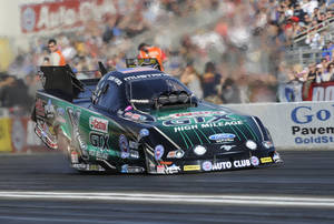 Photo - In this photo provided by the NHRA, John Force races during qualifying position in Funny Car at the NHRA Winternationals drag races at Auto Club Raceway on Saturday, Feb. 8, 2014, in Pomona, Calif. His time from Friday night stood up for the rest of qualifications. (AP Photo/NHRA, Jerry Foss)
