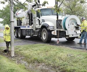 Photo - City  workers use a specially equipped truck to suck up raw sewage dumped into an open ditch in a McAlester neighborhood. (McAlester News-Capital photo)