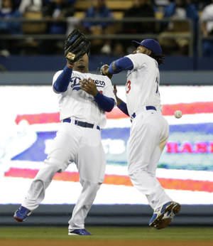Photo - Los Angeles Dodgers' Carl Crawford, left, and Hanley Ramirez misses the ball hit by Philadelphia Phillies' Carlos Ruiz during the 10th inning of a baseball game on Tuesday, April 22, 2014, in Los Angeles. (AP Photo/Jae C. Hong)