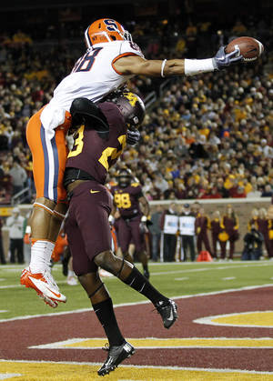 Photo -   Minnesota cornerback Michael Carter, right, interferes with Syracuse wide receiver Jarrod West in the second half of NCAA football in Minneapolis, Saturday, Sept. 22, 2012. Minnesota defeated Syracuse 17-10. (AP Photo/Andy King)