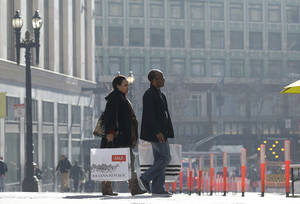 Photo - FILE - In this Tuesday, Dec. 24, 2013, file photo, a man and woman carry shopping bags as they cross the street in San Francisco. The Commerce Department reports how much consumers spent and earned in December. on Friday, Jan. 31, 2014. (AP Photo/Jeff Chiu)
