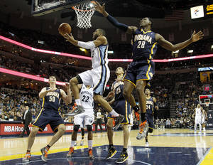 Photo - Memphis Grizzlies guard Wayne Ellington (3) goes to the basket against Indiana Pacers defenders Tyler Hansbrough (50), Gerald Green (25) and Ian Mahinmi (28), of France, in the first half of an NBA basketball game on Monday, Jan. 21, 2013, in Memphis, Tenn. (AP Photo/Lance Murphey)
