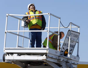 Photo - Above: Workers with Traffic Systems Inc. replace the traffic signal at Robinson Street and Berry Road in Norman.