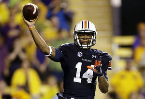 Photo - Auburn quarterback Nick Marshall (14) passes in the second half of an NCAA college football game against LSU in Baton Rouge, La., Saturday, Sept. 21, 2013. LSU won 35-21. (AP Photo/Gerald Herbert)