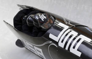 Photo - The team from the United States USA-1, piloted by Steven Holcomb, take a curve during the men's four-man bobsled training at the 2014 Winter Olympics, Friday, Feb. 21, 2014, in Krasnaya Polyana, Russia. (AP Photo/Natacha Pisarenko)
