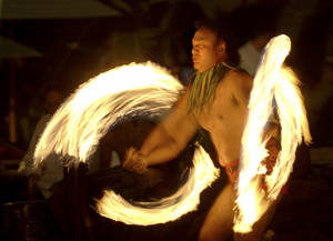 "photo -   FILE - This Feb. 3, 2005 file photo shows Vise Vitale of Honolulu performing a Samoan fire knife dance during in an ""Aloha Friday"" celebration of Polynesian music song and dance in Honolulu. Fire knife dancing is often mistaken for Hawaiian even though it's a Samoan invention. Hawaii resorts are increasingly turning to Hawaii's actual rich traditions to make trips special for travelers. (AP Photo/Lucy Pemoni, file)"