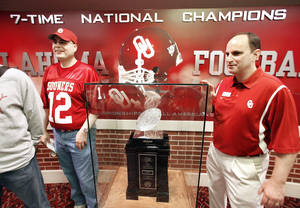 photo - OU athletic director Joe Castiglione, right, poses for a photograph with OU fan William Lawhorn and the Sooners' 2000 national championship trophy.  Photo by Steve Sisney, The Oklahoman
