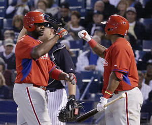 Photo - Philadelphia Phillies' Ryan Howard greets on-deck batter Marlon Byrd at the plate after hitting a third-inning solo home run off New York Yankees relief pitcher Vidal Nuno in an exhibition baseball game in Tampa, Fla., Tuesday, March 25, 2014. Nuno also allowed a solo home run to Byrd in the inning. Yankees catcher Brian McCann is at left rear. AP Photo/Kathy Willens)