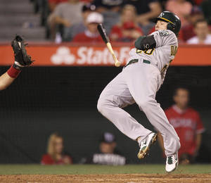 Photo -   Oakland Athletics' Josh Donaldson jumps out of the way of a wild pitch against the Los Angeles Angels during the fifth inning of a baseball game in Anaheim, Calif., Monday, May 14, 2012. (AP Photo/Chris Carlson)