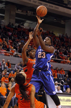 Photo - Auburn's Tyrese Tanner (32) draws a charge from Kentucky's Samarie Walker (23) who shoots during the first half of an NCAA college basketball game on Sunday, Jan. 19, 2014, in Auburn, Ala. (AP Photo/Butch Dill)