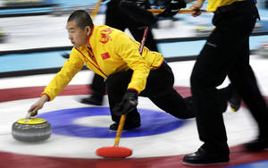 Photo - China's skip Liu Rui delivers the rock during the men's curling competition against Germany at the 2014 Winter Olympics, Wednesday, Feb. 12, 2014, in Sochi, Russia. (AP Photo/Wong Maye-E)