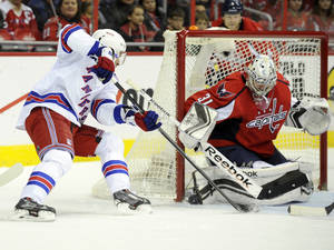 Photo - New York Rangers center Dominic Moore, left, tries to get the puck past Washington Capitals goalie Philipp Grubauer (31) during the second period an NHL hockey game, Friday, Dec. 27, 2013, in Washington. (AP Photo/Nick Wass)