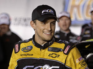 Photo -   James Buscher smiles after winning the NASCAR Trucks Series auto race at Kentucky Speedway in Sparta, Ky., Friday, Sept. 21, 2012. (AP Photo/Garry Jones)