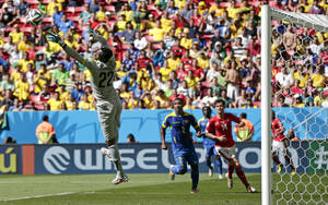 Photo - Ecuador's goalkeeper Alexander Dominguez leaps out to make a save in front of his goal during the group E World Cup soccer match between Switzerland and Ecuador at the Estadio Nacional in Brasilia, Brazil, Sunday, June 15, 2014. At right, Ecuador's Jorge Guagua and Switzerland's Valentin Stocker.  (AP Photo/Marcio Jose Sanchez)