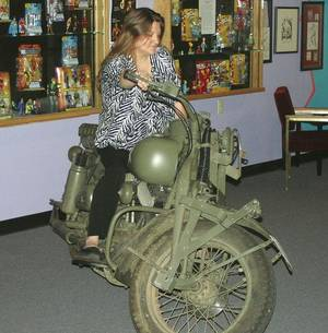 Photo - Jodi Wood, manager of the Toy and Action Figure Museum, sits on one of the cycles used in the 2011 Captain America movie. (Pauls Valley Daily Democrat photo)