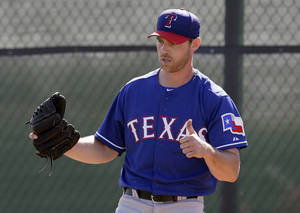Photo - In this photo taken Feb. 23, 2014, Texas Rangers' Neal Cotts gives a thumbs-up after throwing in the bullpen during spring training baseball practice in Surprise, Ariz. Cotts received an unexpected call from the Rangers, and last season made a record-setting comeback. (AP Photo/Tony Gutierrez)
