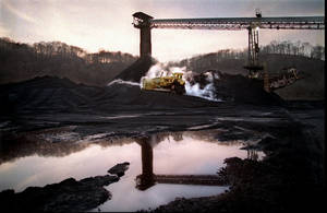 Photo - FILE - In this Dec. 19, 1997 file photo, a bulldozer pushes coal to a waiting train at the Powhatan No. 6 mine in Alledonia, Ohio. The Ohio EPA has allowed more than a dozen coal facilities' discharge permits, including Powhatam No. 6's, to expire since Republican Gov. John Kasich took office in 2011. (AP Photo/The Plain Dealer, Scott Shaw, File) MANDATORY CREDIT; NO SALES