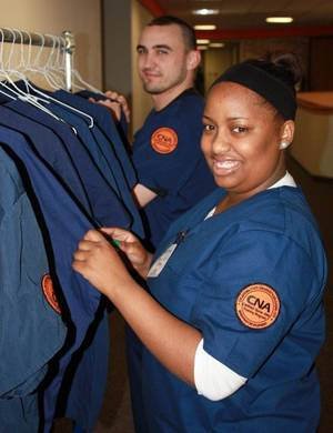 Photo - Oklahoma State University-Oklahoma City nursing students Eugene Albrycht and Fareeda Menser at the program's scrub closet. PHOTO PROVIDED BY OSU-OKC
