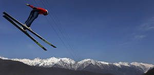Photo - Bryan Fletcher of the United States soars through the air during a Nordic Combined training at the 2014 Winter Olympics, Sunday, Feb. 16, 2014, in Krasnaya Polyana, Russia. (AP Photo/Matthias Schrader)