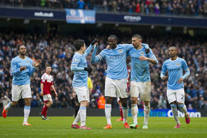 Photo - Manchester City's Yaya Toure, centre, celebrates with teammates after scoring his third goal against Fulham during their English Premier League soccer match at the Etihad Stadium, Manchester, England, Saturday March 22, 2014. (AP Photo/Jon Super)