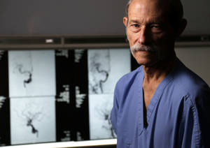 photo - Dr. Timothy Tytle stands Friday in front Mario  Guzman's images before and after surgery for an aneurysm at Mercy Hospital in Oklahoma City.  Photo by Bryan Terry, The Oklahoman