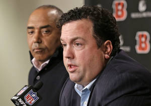 Photo - Paul Guenther, right, answers questions at a news conference with Cincinnati Bengals head coach Marvin Lewis, Thursday, Jan. 16, 2014, in Cincinnati, after Guenther was named the new defensive coordinator for the NFL football team. Guenther, who had been linebackers coach for the Bengals, replaces Mike Zimmer who took the head coaching job in Minnesota. (AP Photo/Al Behrman)