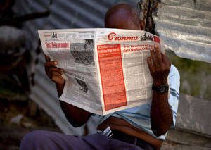 photo -   A man reads a Tuesday copy of the Communist Party newspaper Granma which published the new migratory policy that will no longer require islanders to apply for an exit visa on it's front page, in Havana, Cuba, Tuesday, Oct 16, 2012. The Cuban government announced Tuesday that it will eliminate the bureaucratic procedure that has been a major impediment for many seeking to travel overseas for more than a half-century. (AP Photo/Ramon Espinosa)