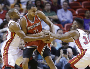 Photo - Milwaukee Bucks center John Henson (31) tries to regain control of the ball from Miami Heat forward James Jones (22) and guard Norris Cole (30) during the first half of an NBA basketball game on Wednesday, April 2, 2014, in Miami. (AP Photo/Wilfredo Lee)