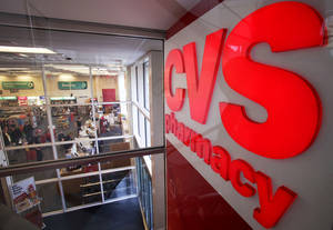 Photo - FILE - In this Nov. 3, 2009 file photo, a CVS pharmacy sign is displayed at a CVS in Providence, R.I. CVS Caremark Corp. reports quarterly earnings on Tuesday, Feb. 11, 2014. (AP Photo/Steven Senne, File)