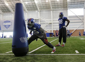 Photo - New York Giants defensive end Damonte Moore (98) looks on as safety Antrel Rolle (26) hits a practice dummy during NFL football practice in East Rutherford, N.J., Wednesday, Nov. 20, 2013. AP Photo/Mel Evans)