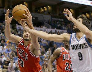 Photo - Chicago Bulls center Joakim Noah (13) pulls down a rebound against Minnesota Timberwolves guard Ricky Rubio (9), of Spain, during the fourth quarter of an NBA basketball game in Minneapolis, Wednesday, April 9, 2014. The Bulls won 102-87. (AP Photo/Ann Heisenfelt)