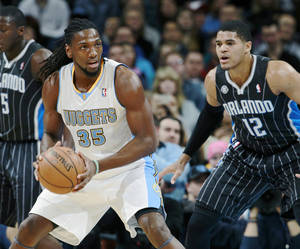 Photo - Denver Nuggets forward Kenneth Faried, left, looks to pass ball as Orlando Magic forward Tobias Harris covers in the first quarter of an NBA basketball game in Denver on Saturday, Jan. 11, 2014. (AP Photo/David Zalubowski)