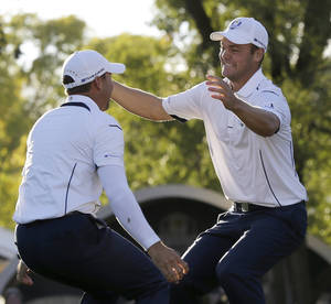 Photo - Europe's Martin Kaymer leaps into the arms of teammate Sergio Garcia after winning the Ryder Cup PGA golf tournament Sunday, Sept. 30, 2012, at the Medinah Country Club in Medinah, Ill. (AP Photo/David J. Phillip)  ORG XMIT: PGA202