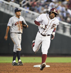 Photo -   Florida State's Sherman Johnson, right, rounds the bases past Arizona's Alex Mejia, left, after Johnson hit a solo home run in the third inning of an NCAA College World Series baseball game in Omaha, Neb., Friday, June 15, 2012. (AP Photo/Eric Francis)